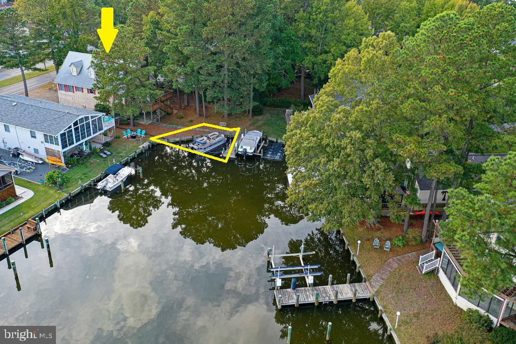 Spacious furnished 3000 Square foot home with a boat dock and access to St Martins River and Assawoman Bay with no bridges in the desirable community of Ocean Pines.  Enter the home to a warm and inviting ground-level Living area with a brick/masonry fireplace which has been converted to an Electric insert with a blower.  This level also includes a heated storage/laundry area with access to the two-car garage.  Large rear patio to relax and enjoy the canal views.  New Insulated Garage doors with new openers, front entry, and rear entry doors are on order and are to be installed soon.   Wireless, smartphone (or internet) controlled thermostat for heating and cooling.  The main level boasts a large open floor plan with Maple cabinets in the kitchen, a second wood-burning fireplace, master bedroom, 2nd bedroom, and full hall bath.  Large 2nd floor rear deck leading to stairway and large partially wooded back yard and dock for your boat.  3rd floor has extra large bedrooms perfect for summer guests with a full bath.  Thoughtful planning during build allowed for pre-plumbed space for kitchenette/sink on the third floor. Hardwood floors throughout.