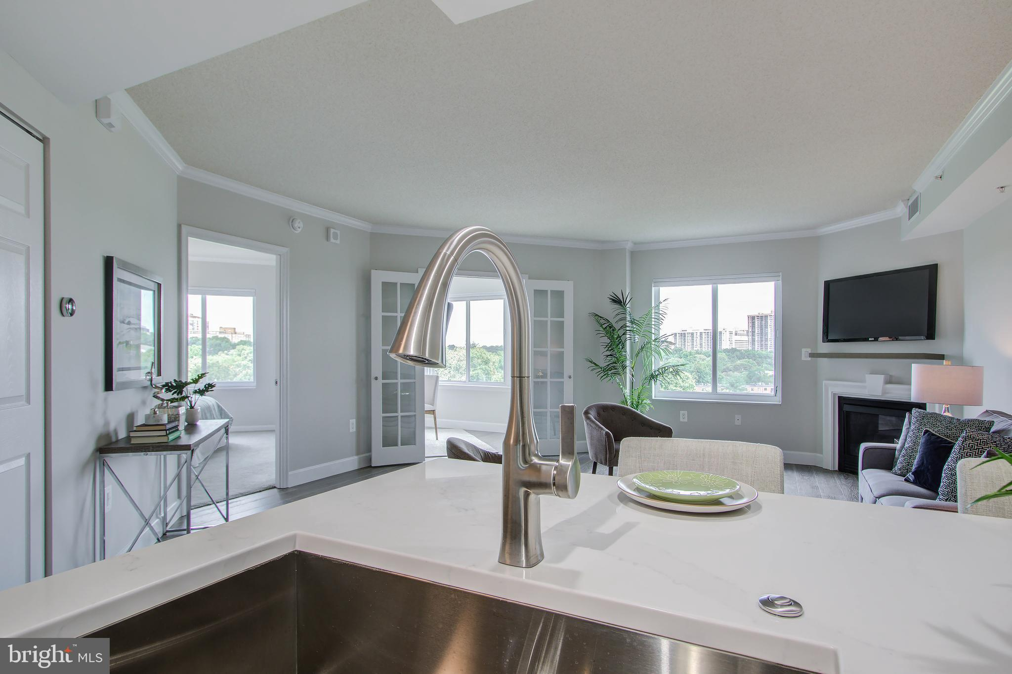 The best in its class...  stunning, chic and modern. This Luxury Collection 1-bed/1-bath with den is the first fully renovated 1-bedroom to be sold in the Northampton Place Community. With over $40K in renovations, this unit features an open floor plan and everything you've ever dreamed of! Starting with the beautiful and durable next generation Torino White Oak wire brushed water-resistant engineered hardwood flooring installed in the entry, kitchen and living areas coordinating with the modern gray-tone wall paint used throughout. Moving to the gourmet kitchen: refinished/refreshed kitchen cabinets with added soft close doors are complemented by a beautiful quartz countertop, Adessi Zellige pearl opal polished ceramic tile backsplash, Lyric stainless steel large single bowl sink with SilentShield sound absorption technology and Kohler Rubicon single-handle faucet. The appliances have been replaced with high-end fingerprint resistant stainless steel type from the Frigidaire Gallery Collection. The  kitchen update package is completed with a top-of-the-line sound reducing technology 3/4 HP continuous feed garbage disposal. The den design features French doors and  breathtaking panoramic windows making it a perfect space for working or lounging. And the den and living room window blinds have been replaced with new Bali light filtering top-down bottom-up cellular shades for optimum light, plus privacy. We've even added provisions in the living room which allows you the option of locating your TV above the fireplace. In the bedroom we've added new quality Shaw stain-resistant carpet and a Bali blackout top-down bottom-up cellular shade to the window. To maximize space utilization, bedroom and coat closets include Elfa organization systems. Moving to the bathroom - it has been renovated with new porcelain floor and wall tile, Carrara marble countertop, modern fixtures and a new Kohler soaking tub. We've even added a new LED light above the tub. But wait - we're not done