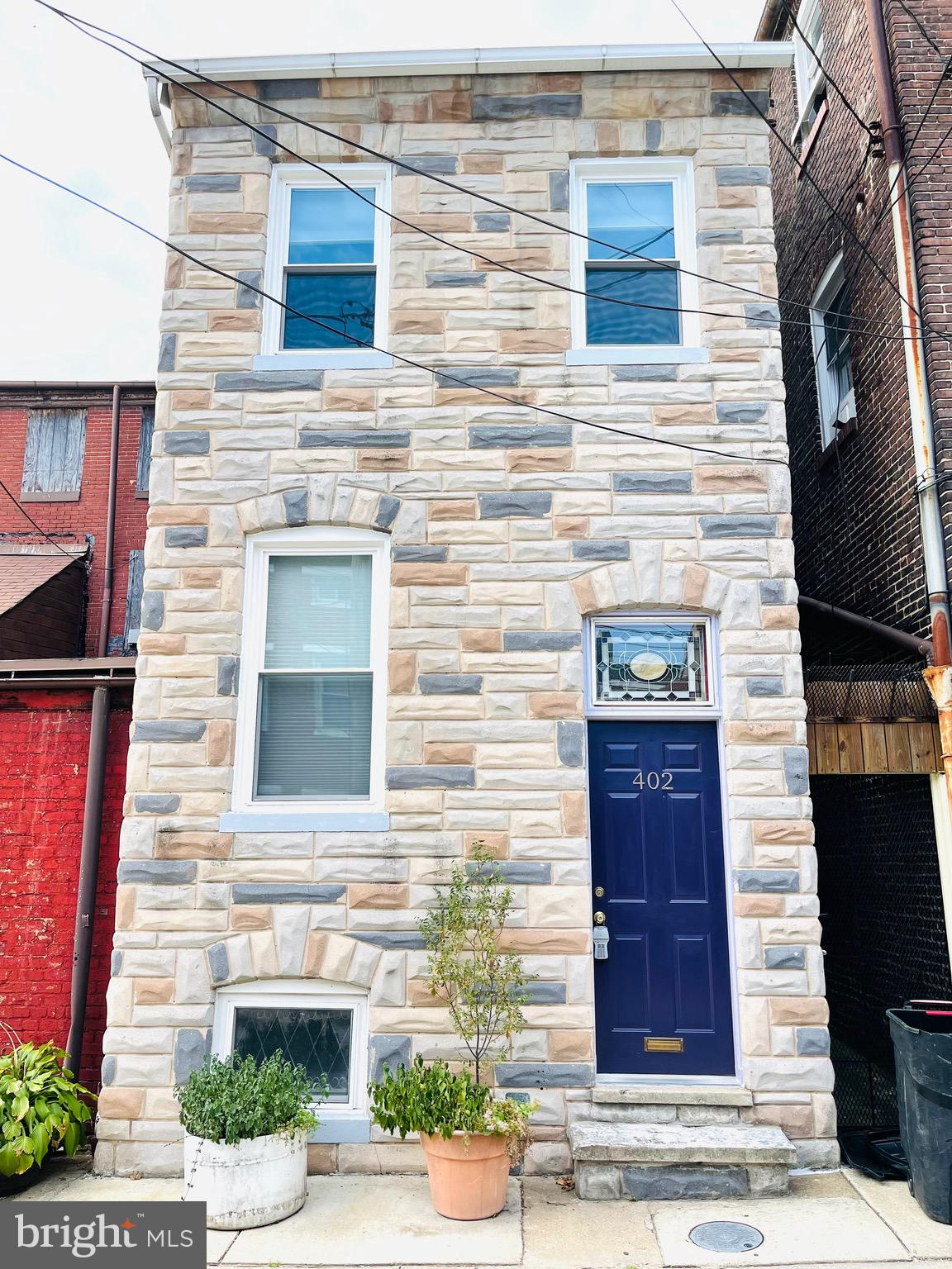 Come see this adorable house located on a quiet alley street in Fells Point!  This house has 100% Baltimore personality!  Many original features are still in-tact such as the original tin walls (repurposed from the kitchen ceiling) and transom window in the vestibule, wood paneling salvaged from an old bank on Eastern Ave throughout the living room/dining room and the mantle in the primary bedroom.  Exposed brick and hardwood floors throughout the house.  Open kitchen concept containing plenty of cabinets and a breakfast bar that overlooks the quaint English garden, which is filled with an abundance of greenery.  Primary bedroom has a generous-sized closet with an en suite bathroom.  Additional bedroom on the second floor has original wood floors, two closets and a large interior round window and an en suite bathroom.  The private attached full bath has the ever-popular claw foot tub and tons of natural light. Large room on the third floor is perfect for a bedroom, office or dressing room.  Full, clean, dry basement holds the washer/dryer, plenty of storage and workspace for creatives.  Four Mitzubishi Split Units easily cool the house. New roof, new windows in 2019. New furnace in 2018. Walk right into Fells Point, short walk to Harbor East and Hopkins Hospital.  This home retains its original charm, if you want the real deal, come and see this house!