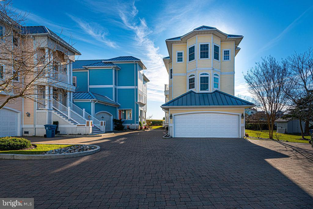 Enormous views without  the enormous price!! Located in the private neighborhood of Harbor Lights, once entering your friends and family will never want to  see the Ocean City fireworks from anywhere but here. Enjoy the expansive views of downtown Ocean City, Ocean City, Ocean City Inlet and Assateague Island right from any one of the three wrap-around decks or head over to Gudelsky Park where  you can enjoy some great surf fishing to catch your dinner. This estate style home is also conveniently located near  many great West OC restaurants, shopping, boating, and the beach.  As you enter the home you are greeted by your In-law suite, Guest quarters, Mediaroom, Captains quarters, you name it! The second level is the Master bed room suite which has its own fireplace, wet bar, refrigerator, and wrap around deck.  Massive  bathroom with executive closet.  this level also offers convenient laundry room just out side your master suite.  There is an additional bedroom with a walking closet and  en-suite.  Last but not least the top floor has all the elegance and class you have been wanting. All the hardwood floors throughout the living areas have been refinished.  The living area with all of it's beauty has a gas fireplace and custom built in shelving and epic sliding glass doors surround the living room where the view is the artwork and the subject of many conversations.  Watch endless sunrise and sun sets from this wraparound open-air deck  .  Sunbathing, grilling, bird watching, people watching or just relaxing .  Now while entertain you 'll be cooking in your state- of-the- art gourmet kitchen  with spacious custom cabinets, center island, stainless steel appliances and still be part of the fun.  The fourth bedroom with walk in closet and en-suite is located on this level.  Come start your Coastal Life style Living today.