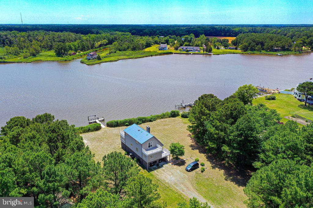 """This is a One-of-a-Kind location with breath-taking views! A secluded 2.5 acre waterfront """"Island"""" Paradise can be yours to enjoy while the weather is still perfect!  Walk out your door to your environmentally-friendly soft shoreline which features a brand new private deep-water dock with lift, and head straight for the Bay and the Atlantic Ocean! Extensive inside and outside renovations have been completed including a metal roof, granite countertops in the island kitchen, skylights, fireplace, a space-saving Murphy Bed, and so much more!  There are four balconies/decks, a 12x18 storage shed with workbench,  2 large climate-controlled storage areas under the home, and  covered parking for 5 cars or for your Boat! Even better,  most of the furniture will convey.  One Year Warranty will be provided to Buyer.   Be in your new home this September!   Call today to see this magnificent property and all that it has to offer!"""