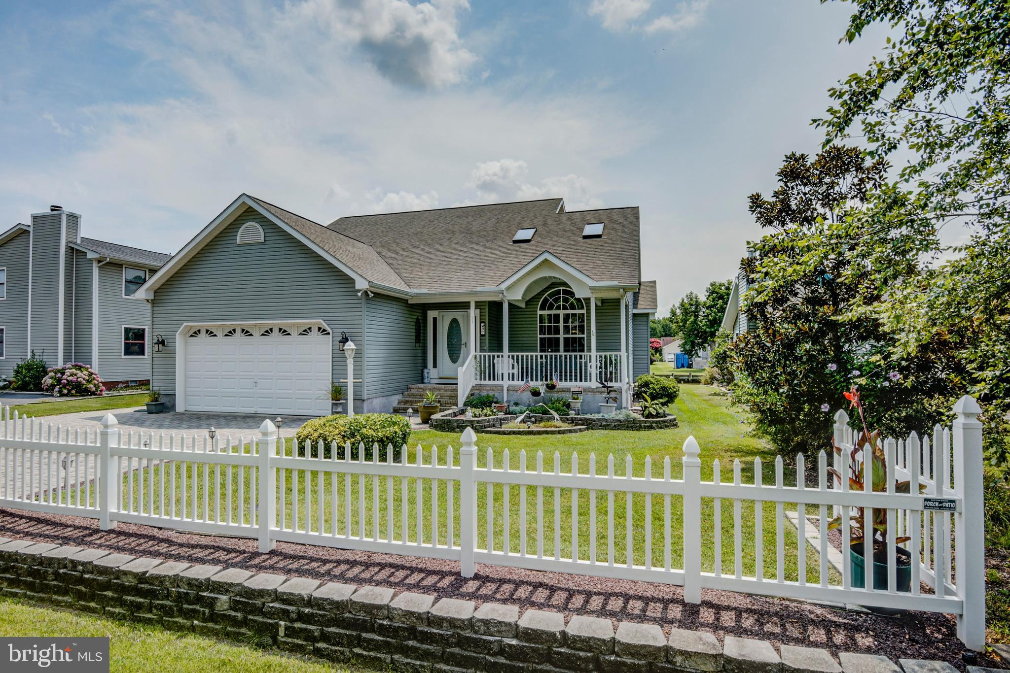 Immaculately maintained waterfront home with sunroom, three-seasons room, hardscaped patio, boat doc