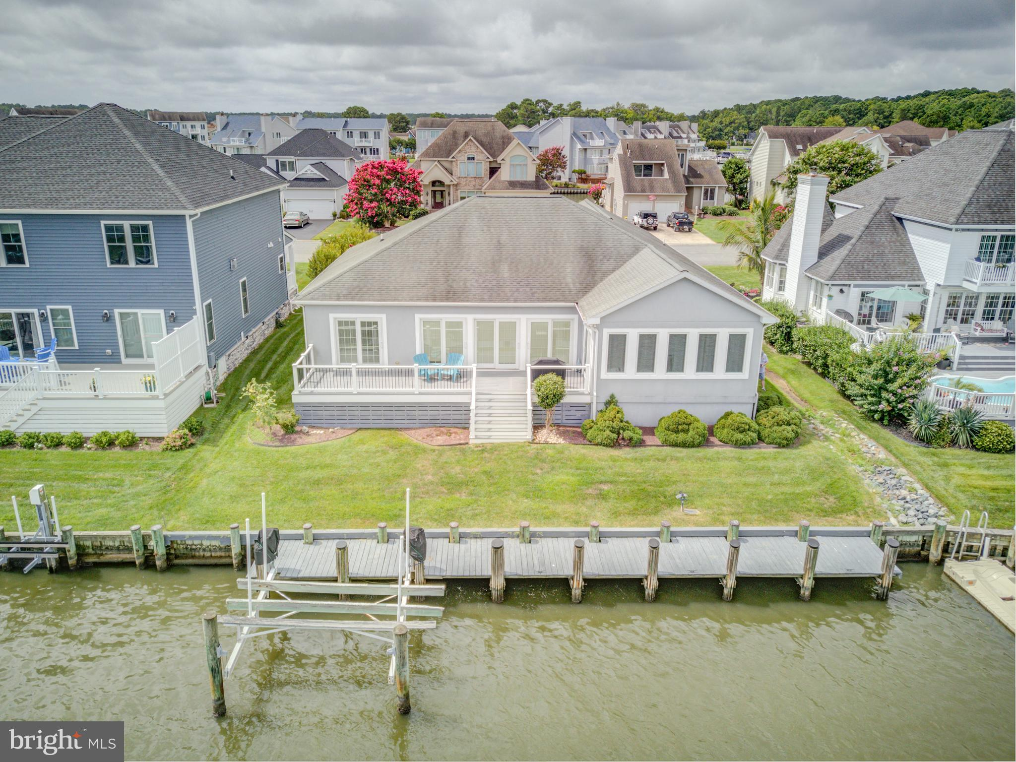 NEW PRICE . Dreams do come true! Looking for a waterfront 1 level custom-built home with boat dock and lift with quick access to Bay and Ocean? Look no further. Very large open Living and Dining room with tile floors and lots of windows. Gas Fireplace added and TV included. Sun Room/den directly off that with access to large rear deck with gas grill hooked up to central line. Primary bedroom has a primary bath with walk-in closets, shower and separate areas with twin sinks. Laundry room with Bonus/Office room off to one side and pantry closet for additional storage. Large kitchen with great bar seating plus a desk area and pantry. 2 car garage and concrete driveway. 60 ft. long pier with boat lift.  Nice rear yard. Remaining furniture will stay along with 4 TVs and Surround Sound system. Ready for your enjoyment immediately.