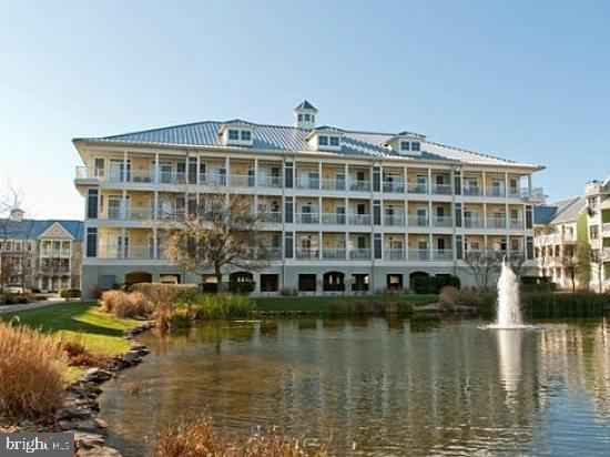 Come see this corner condo with its ideal location.  Ready to move in and enjoy the sights and sounds of the beach.  Located right on the pond, just a short distance to the clubhouse/pools,  interactive fountain, the walking trails and only a few short walking blocks to the Atlantic Ocean.  You can even catch a glimpse of the bay from your back porch.  This one level condo is spacious and open and has lots of light.  The cheerful interior is one level and has roomy bedrooms and bathrooms.  The building features a lobby with elevator, ground level extra storage, covered assigned parking, outdoor shower and trash chute.  Start enjoying the best of luxury living at Sunset Island today with this property.  You will love the location, surrounding natural beauty and easy access to everything.