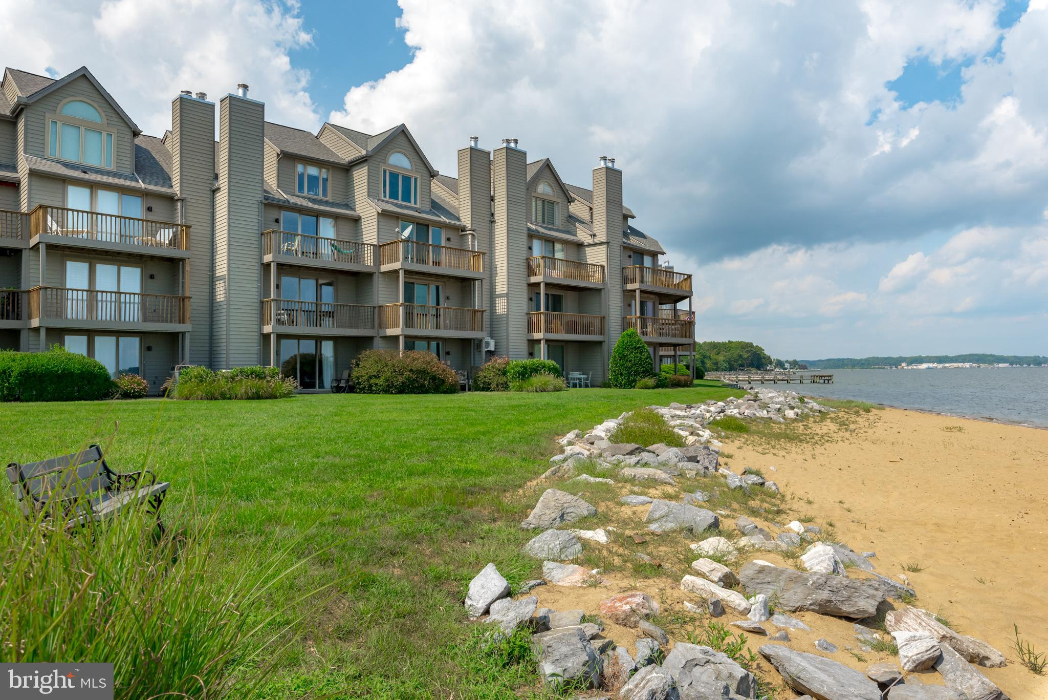 Luxurious Townhome offering  expansive water views of the Chesapeake Bay and Bay Bridge. Wake up to the sounds of waves and views of the beach below!  Home features 4 levels of breathtaking views with an elevator for easy access to all levels.  Updated all-white eat in gourmet kitchen. Remodeled large Primary Suite with waterfront deck, dual walk-in showers and double vanities. All the bedrooms have been updated to include custom cabinetry, solid wood doors and crown molding. All hardwood floors and recent exterior sliders. One car garage and workshop . Walk out the lower level opens to the fabulous community beach. The gated community offers amenities that makes you feel as if you are on vacation all year round.  Two pools, four tennis courts, jogging and walking paths, piers, kayak launch, marina, beaches as well as Sam's Waterfront restaurant with its very own tiki bar. Minutes to Downtown Annapolis and a short boat ride down ego alley. Easy commute into Baltimore and Washington, DC.