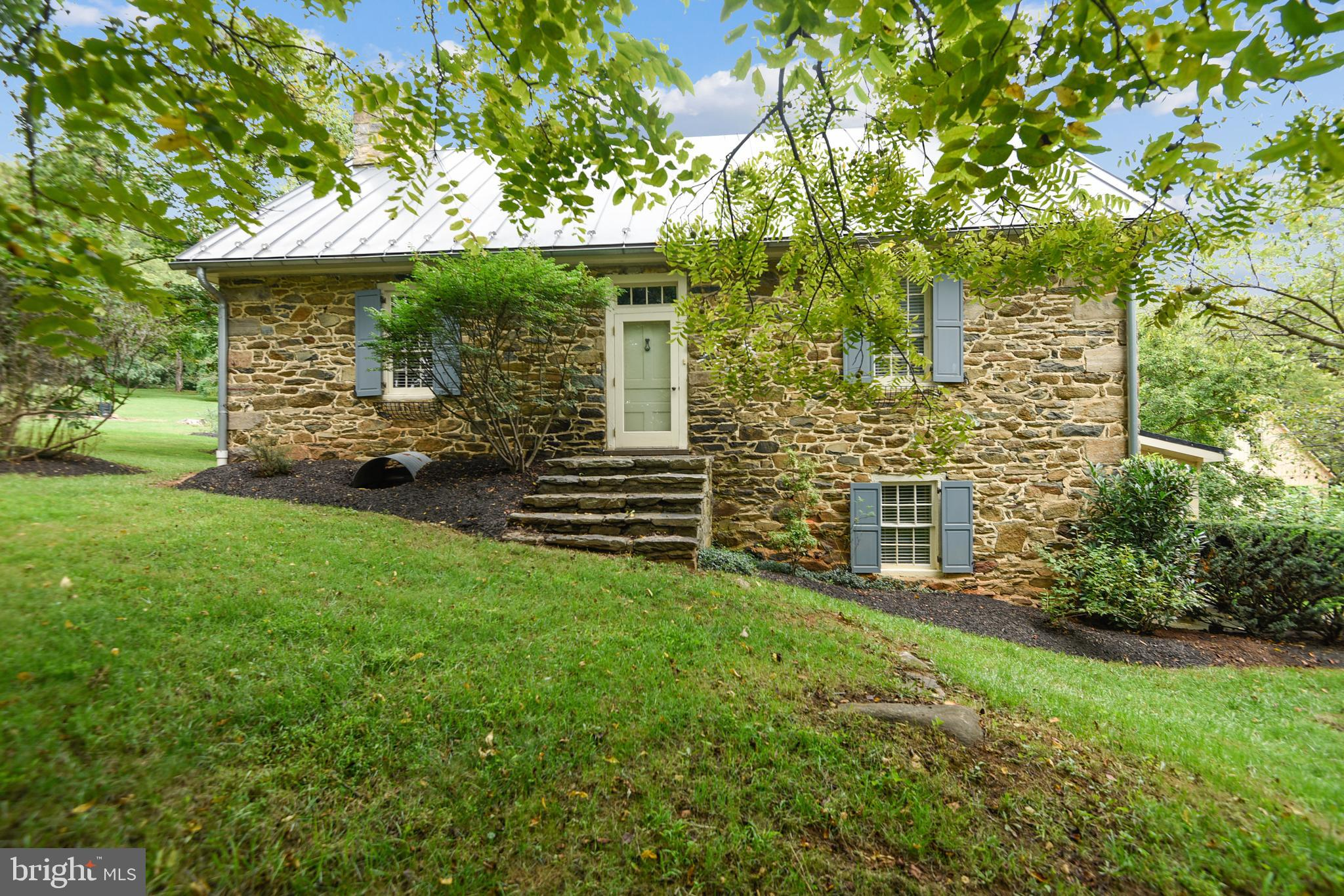 """Take a step back in time as you view this historic property built in the 1780's. Let the sounds of nature surround you as you explore to catch a glimpse of secluded spaces that beg to be enjoyed. Many added features and updates demonstrate the loving care of those entrusted with its stewardship.  In 1995, the present homeowners had extensive renovations completed and an addition put on the back of the original stone house.  Their goal was to preserve the historical aesthetics and maintain the integrity of the property while adding tasteful improvements for twenty-first century convenience.  The main and upper level of the original structure has been handsomely preserved.  The home offers four bedrooms (with potential for a fifth bedroom), and three full bathrooms.  The original kitchen and root cellar on the lower level have been converted to family and dining space and a wonderfully inviting kitchen.  Main and upper level patios and balconies at the rear of the addition give you views of the stunning acreage and outbuildings.  The home sits on a 15-acre parcel with beautiful landscaping, pebble walkways and stone walls.    The original summer kitchen with loft remains.  Oversized two-car garage with hay loft and electricity offers additional space.  Outbuildings include corncrib, one-story barn with original stone foundation, forty-foot pole barn on concrete slab, machine shed, and spring house sold """"as is""""."""