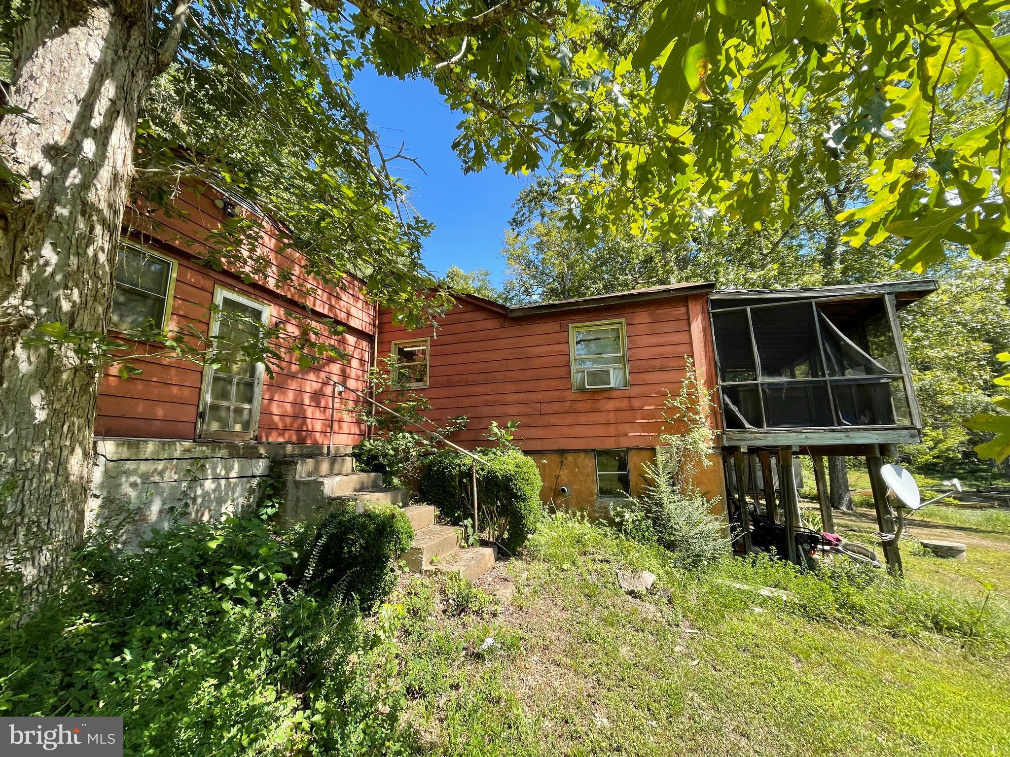 ATTENTION INVESTORS & CASH BUYERS! This diamond in the rough can become your opportunity to create an incredible waterfront home just minutes from town!  And, without the HUGE waterfront price! Maybe you're dreaming of your very on AIRBNB? Maybe you're wanting a get-a-way of your own?  Who says you can't have both?    With almost 3 acres, you can ENJOY privacy, fishing, beautiful flowers and nature all around you! Take a short walk over the bridge and explore what's on the other side! Explore the lake by canoe! There's plenty of space to explore and even create even more trails! Don't let this opportunity pass and you miss out on all of your dreams! Explore those dreams and make them a reality!! Those dreams can create income and/or your very own get-a-way! This gem is conveniently located in Spotsylvania, near the courthouse area,  schools, shopping, dining & medical offices!