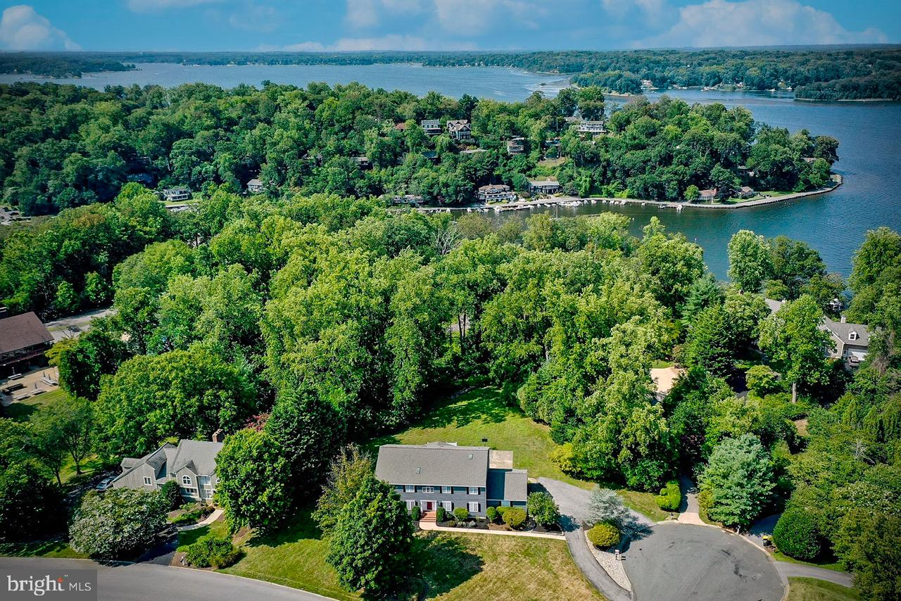 Renowned Downs on The Severn  Waterfront & Water Privileged Annapolis Community with 2 Deep water Marinas, Clubhouse, Tennis Courts and community pool!  Located almost at the end of Coachway on Cul-de-sac with large level lot and almost 5,000 sq. ft above grade and  7,000 sq. ft of potential living space with huge unfinished basement.  2 Main level bedroom suites plus a main level office offer flex space for multigenerational living.  Recently refinished Hardwood flooring throughout almost entire Main level with 2 Story Entrance and Great room with skylights.  Screened porch for crisp fall evening dining and lots of yard space and patio area for play.   Brand New Roof, 3 Car Garage & additional 4 enormous sized Bedrooms on upstairs level with huge loft area.  Winter water views from 2nd floor bedrooms and loft. Custom quality built home home with Anderson & Pella window and doors, Cherry cabinets, Beveled Edge top of the line Corian Counters with integral kitchen and wet bar sink and diagonally laid tile in baths & laundry.  Updated  Hot Water heater (2018) and HVAC (2013)  Come Experience the unique opportunity to Live in The Downs on The Severn!