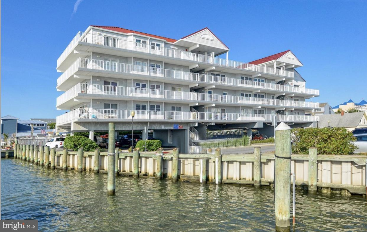 This is the one you've been waiting for! This property is truly special and quite the rare find! This 3 bedroom 2 bathroom penthouse located on the open bay is in absolute pristine condition with panoramic water views. Unit conveys with a 40 foot protected, deeded boat slip located inside the marina basin (slip #3) Marina is located on the south side of the Rt. 50 drawbridge.  Expansive, panoramic views of the open bay, marina, Ocean City Inlet, Assateague Island, West Ocean City, and the Rt. 50 bridge from every room. Unbelievably huge private wrap around south and west facing balcony.  Brand new windows and doors throughout the unit, new siding, roof and secure elevator, recently installed in the building. Unit offers complete privacy because it's the only unit on the 4th floor of the building. Community amenities include: marina, outdoor pool, waterfront gazebo, picinic, seating/relaxing, and dog walking areas.  Slip owners pay a $1,200 per year marina fee due in two $600 semi-annual installments. Special assessment payments are paid quarterly through the last quarter of 2024.  When nothing but the best will do this is absolutely the property for you! Be sure to click on the video icon to see the incredible views.