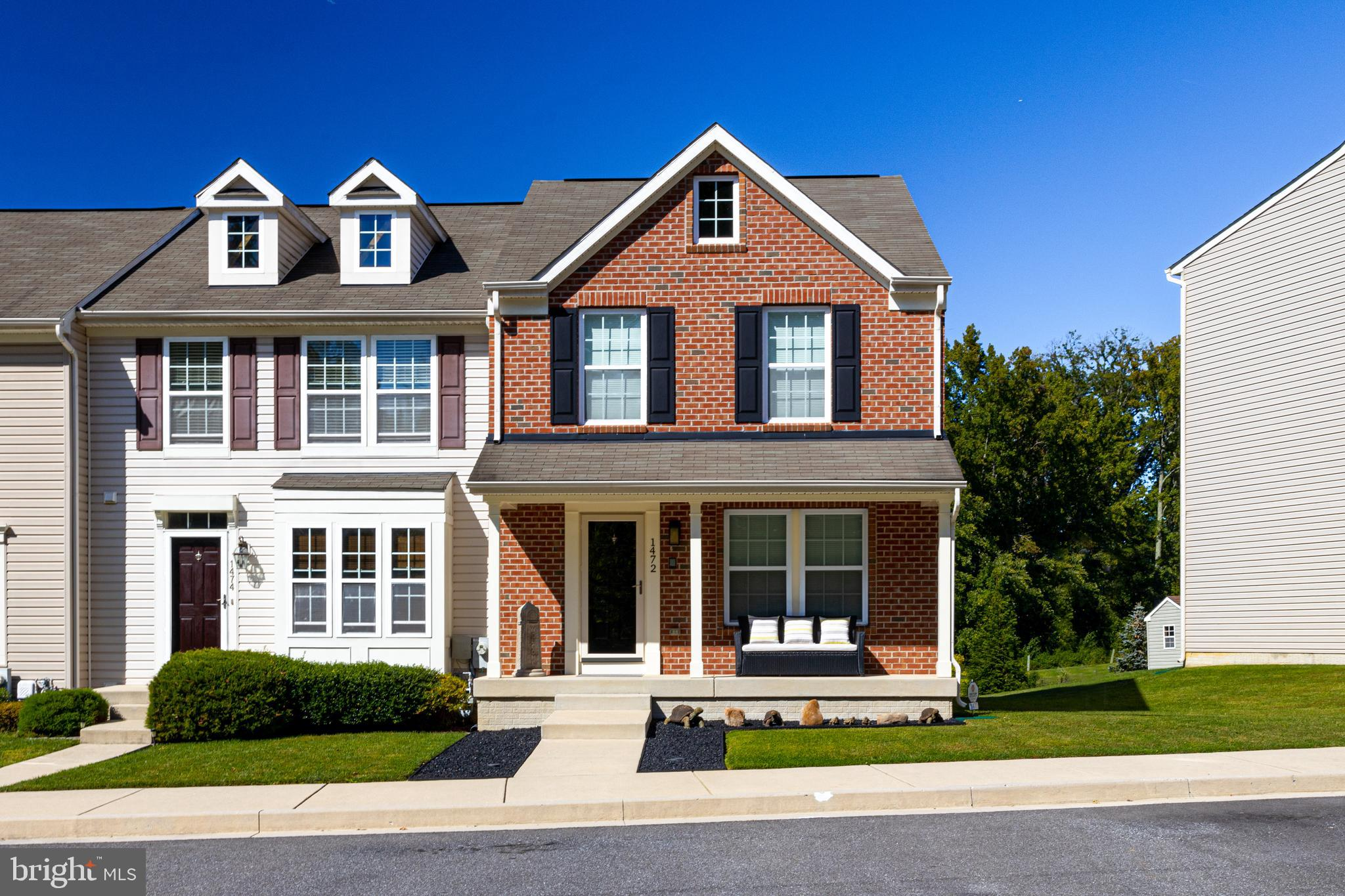 Impeccable brick, porch-front end of group town offers instant curb appeal with its freshly painted