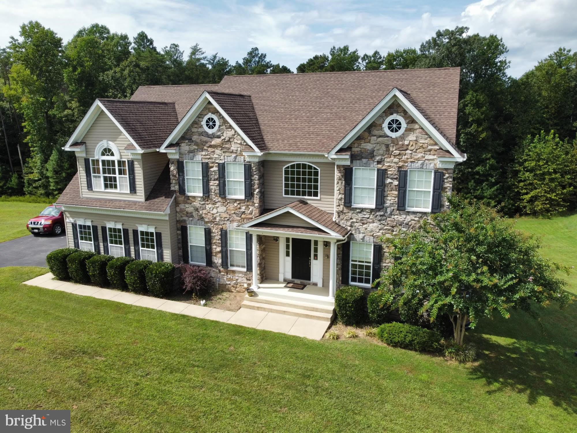 Your dream home awaits in the sprawling, picturesque neighborhood of Ben Oaks in Mechanicsville. Situated on over two gorgeous acres, this stone façade colonial will amaze and excite you.  The home features over 6,000 square feet of many builder upgrades and enhanced finishes.  You will love the gleaming hardwood floors throughout. You will find a total of 4 large, airy bedrooms and 3 and a half baths.  Upon stepping into this warm and inviting home, you will feel the sense of stately elegance in the bright, open foyer. Turn to your right and enter the beautiful, bumped-out living and dining room spaces.  On your left, you will notice the perfect space for a home office or additional sitting area.  Move through the foyer down the hallway to the vast gourmet kitchen featuring stainless steel appliances, two wall ovens, granite countertops, and a large island. Just off the kitchen is the sizable, extended morning room that pours in an abundance of natural light and provides plenty of additional space for seating and entertaining.  The open floor plan allows for a fluid space between the kitchen, morning room and family room area.  Gather around the cozy stone-front gas fireplace in the enormous family room.  Upstairs, the expansive owners suite boasts a separate sitting area, hardwood floors and more than enough space for your king sized bedroom set. The owners suite also includes a lovely breakfast bar with sink and refrigerator.  Dual walk-in closets provide plenty of storage space.  The ensuite bath offers dual vanities, a separate shower and soaking tub with jacuzzi and isolated toilet.  This home is so expansive, you will appreciate the whole-home intercom system with built-in speakers.  Explore the gigantic finished basement that includes a theatre room with projector system hook-up.  Also find a full bath.  This basement is the entertainer's dream.  The basement is plumbed for a bar with sink.  The storage possibilities are endless.  An oversized two-car garage