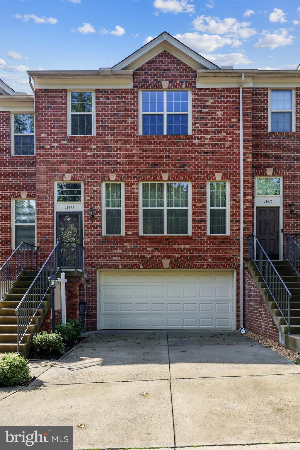 Great new price on spacious, bright and beautiful 9 year young  Centreville townhome! This elegant brick front luxury townhome is on a quiet tree lined enclave of only 10  unique homes.  3 finished levels, 2 car garage, every upgrade you  can imagine. Gleaming hardwoods on the main  & upper levels.  Gourmet kitchen with  granite counters and stainless appliances. Sun-drenched breakfast room opens to  custom composite deck backing to trees. Formal dining room and living room separated by two sided gas fireplace. Upper level  master bedroom suite with luxury bath. 2 large extra bedrooms. Lower level walks out to fenced patio. 4th bedroom, recreation room, full bath and brand new carpet ! All of this in a  convenient  Centreville location. Minutes from the Metro Kiss & Ride, 66, Dulles Airport and Manassas Battlefield Park. Great school pyramid!