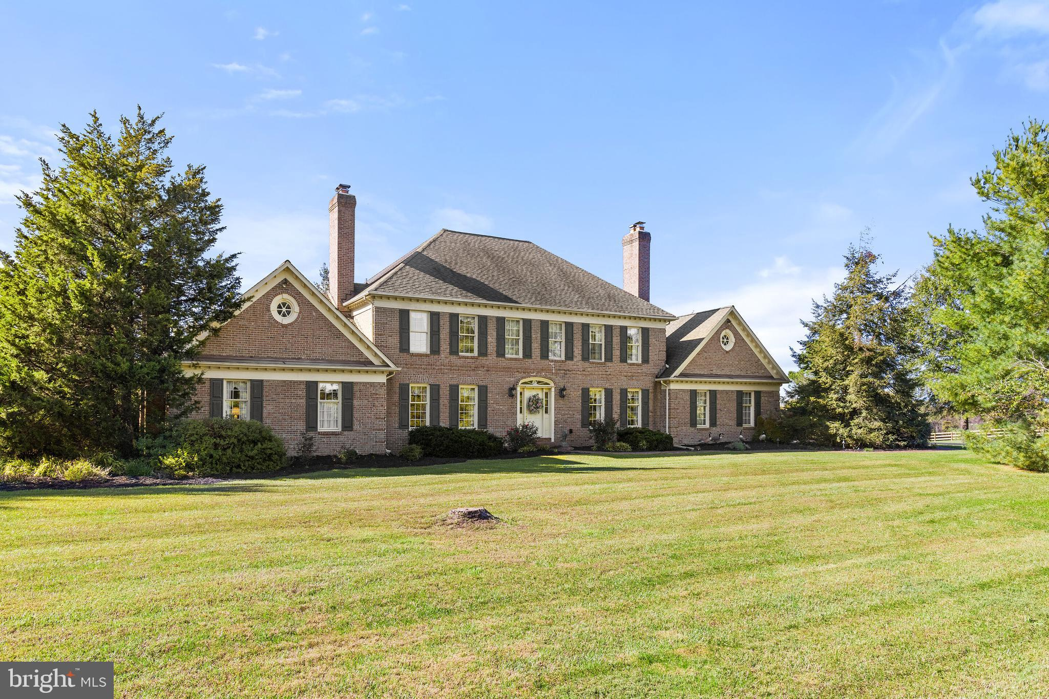 A well-built & meticulously maintained twin chimney brick colonial on 15 acres with a 3-stall barn. This lovely home was custom built by it's current owner and maintains a traditional center hall colonial style floorplan with hardwood floors on the main and upper levels as well as exquisite molding and details throughout. No 'cookie cutter' home here! For the visionary, this home with some updates could be a real show stopper! Room to add a pool or perhaps renovate the workshop/office space (23x23) with a separate entrance into a main level primary suite. The upper level has a 17x17 Primary Suite w/fireplace and hardwood floors. The other two bedrooms (ensuite) have hardwood floors as well. A nice sized kitchen w/granite and exposed brick walls surround the 6 burner cooktop and double ovens. Step down into a cozy family room w/fireplace, bay window and direct access to the back patio. The den/office space w/fireplace can be utilized as a 4th bedroom as the 1/2 bath and closet are located just off the hallway. There is a second full bath off of the laundry room. The formal living room and dining room are located conveniently off of the center hall foyer and both have fireplaces. Add some fencing and you're ready to bring the horses, etc. Not wanting to have horses? Then maybe you'll want to convert the barn into a woodworking space, or the ultimate party barn! So there are many options to consider with this superbly built and well-located property!