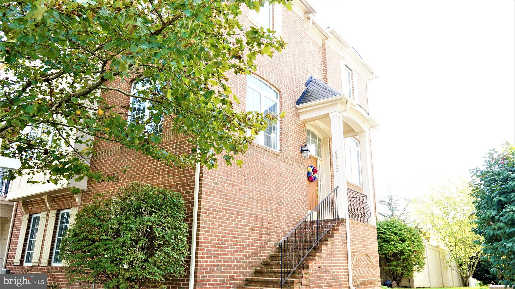 This is a Stunning Brick Front End Unit Townhome with curved Stone Walls + Stone Patio in Private Fe