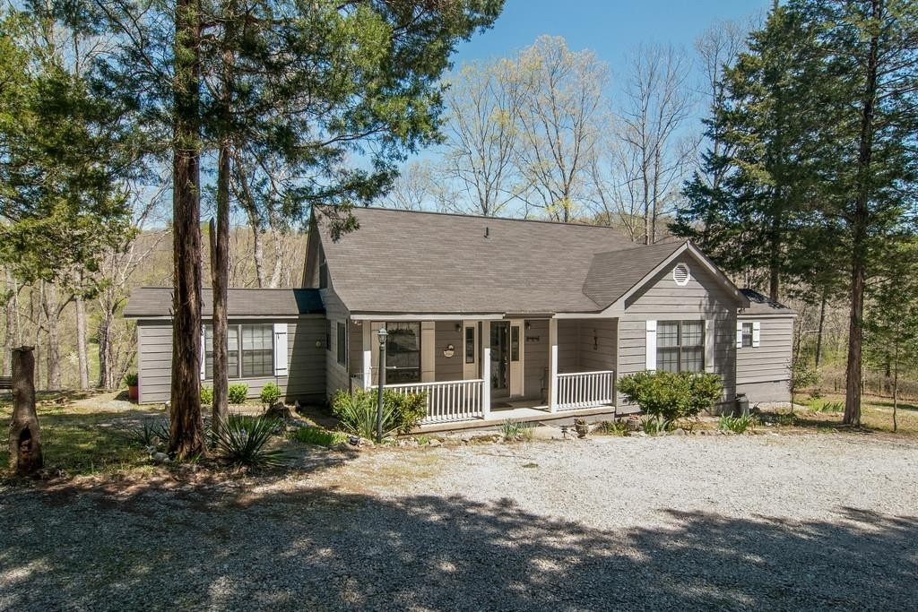 124 acres of pastures and woods with a charming rustic western cedar home on top of the hill with a