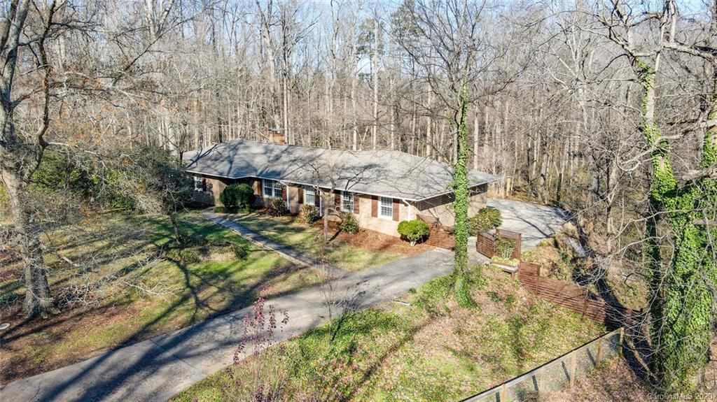 Your sanctuary just minutes from uptown Charlotte. Gorgeous full brick home on over an acre, bordered by streams & pond. Heavily wooded, blooming dogwoods, hardwoods, landscaped with unique trees, exotic plants and shrubbery.  French drained perimeter.  Richly renovated inside by high-end designer.  All new HVAC (to be installed early Jan 2021), new roof, tilt windows, water heater, new 2020 basement split system heating & cooling.  Renovated bathrooms.  Completely new gourmet kitchen with new appliances, convection oven, stove with custom drafted hood.  Delightful imported English wallpaper, custom shiplap, new Alder wood beveled glass front entrance, new interior shaker doors throughout. Endless possibilities with 30 amp & plumbing in bas