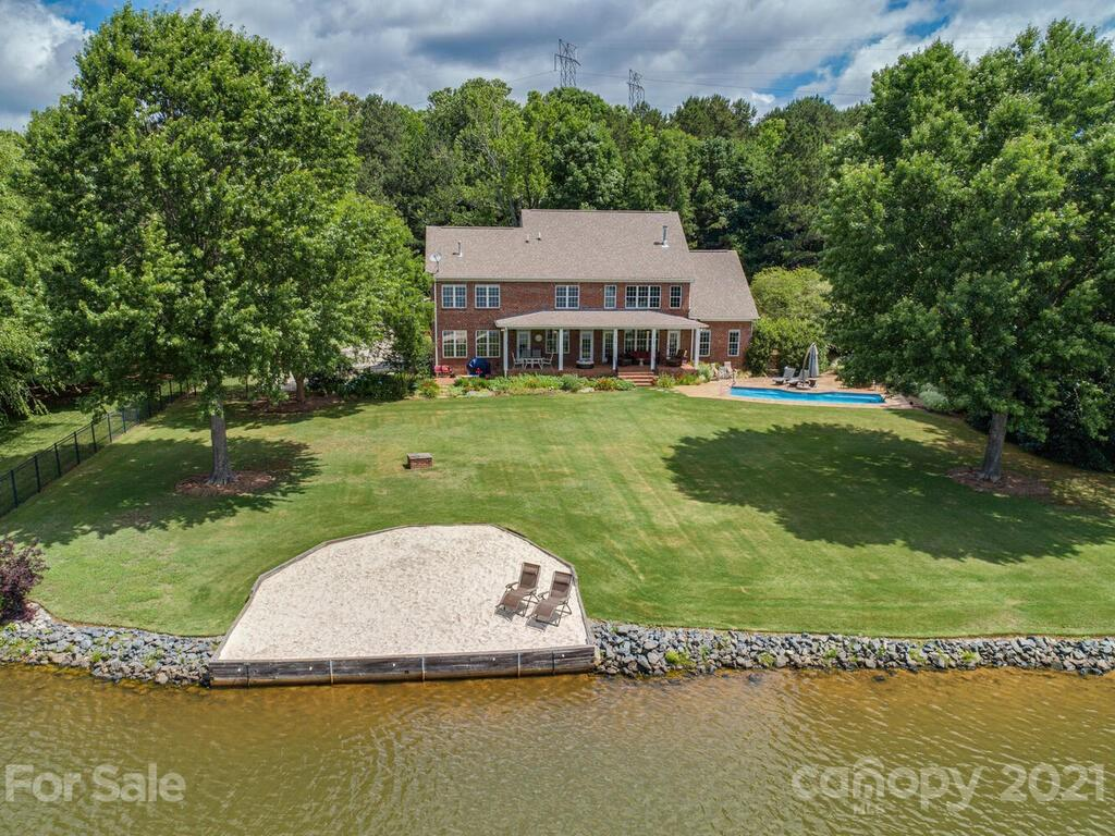 Own a piece of paradise! Your own private resort!  275+ ft. of shoreline views of a 60 acre lake. Private sandy beach area! Fishing/boat dock and launch area for personal non-gas operated watercraft! Over 3.5 acres! Heated salt water pool with swim jets! Views from almost every window or from the 40' rear porch! Perfect place to watch the sunrise & sunset! Terrific home for entertaining and/or just plain relaxing! Quiet, private location at end of private cul-de-sac. Extensive, professionally designed & maintained gardens. Landscape lighting, full irrigation using lake water. Bright kitchen with granite counters, 16' tile, hardwoods, heavy molding, French doors. Master on main with HEATED master bath floor. Bedroom/Bonus large enough to be