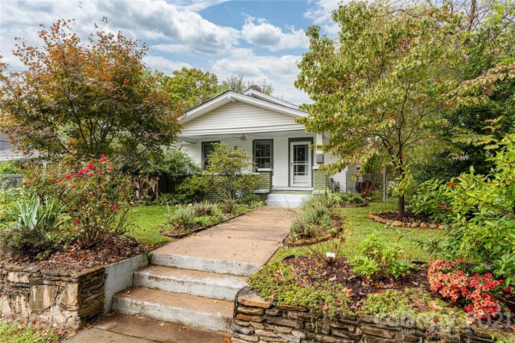 Come grab this West Asheville Gem!  Ideally located in the heart of West Asheville, just one block back from Haywood Street's notable dining and shopping scene, this 1923 Craftsman bungalow features many updates without any loss of charm. Enjoy entertaining with family and friends in the beutifully designed large kitchen featuring hand-built cabinetry, soapstone counters, and Energy Star stainless appliances. Beautiful bathroom with marble walk-in shower.  Original hardwood floors throughout, open floor plan and tons of natural light. Super efficient natural gas furnace and hot water heater with AC . Wonderful outdoor spaces, rocking-chair front porch to enjoy the gorgeous flower gardens, covered back porch off kitchen with access to the ra