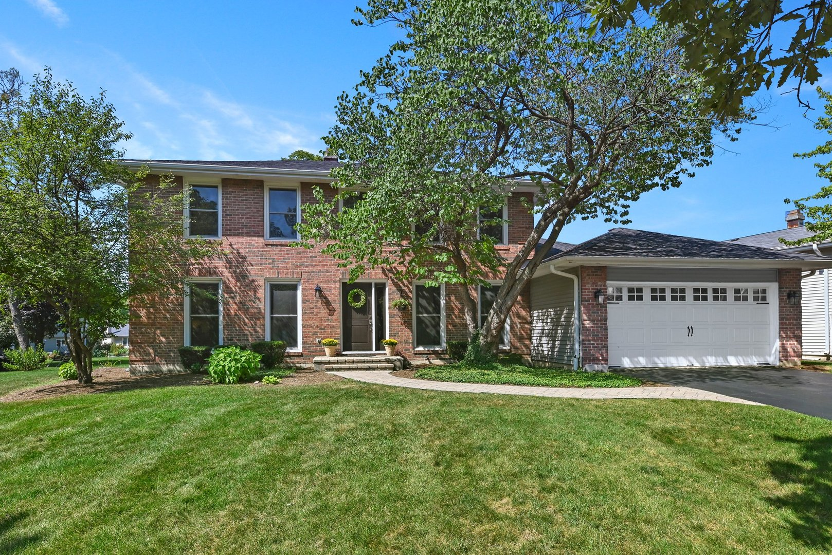 Updated brick Georgian on quiet tree lined street.  Newer eat-in kitchen with granite counters, hardwood floors, large pantry and SS appliances. Butlers Pantry (Gallery) adjacent to kit. and family room. First floor office plus an additional office area in the basement, great for working from home. Spacious living room has refinished hardwood floors and large windows that bathe the room in light. First floor family room with fireplace opens to 12x17 deck with pergola canopy. 2.1 baths, have all been remodeled. Freshly painted interior in '21. New carpet in 4 bedrooms '20. Roof new in '14. New garage door and exterior doors in '20. Finished basement with rec room, office and laundry room for extra living space.  Professionally landscaped yar